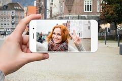 Ο ταξιδιώτης γυναικών επικοινωνεί μέσω ενός smartphone Στοκ φωτογραφία με δικαίωμα ελεύθερης χρήσης