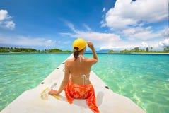 Ο ταξιδιώτης γυναικών κάθεται στη βάρκα στην ηλιόλουστη ημέρα και το κοίταγμα στο καθαρό s Στοκ εικόνες με δικαίωμα ελεύθερης χρήσης