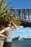 Ο ταξιδιώτης γυναικών προσέχει το ηλιοβασίλεμα από τη λιμενική γέφυρα του Σίδνεϊ Στοκ φωτογραφία με δικαίωμα ελεύθερης χρήσης