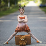 Ο ταξιδιώτης μικρών κοριτσιών με τη βαλίτσα και Teddy αντέχουν είναι στο δρόμο Ευτυχής Στοκ φωτογραφία με δικαίωμα ελεύθερης χρήσης