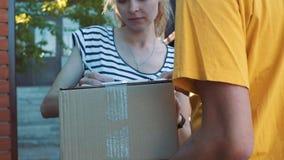 Ο ταχυδρόμος παραδίδει ένα δέμα για μια νέα γυναίκα απόθεμα βίντεο