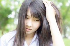 Ο ταϊλανδικός έφηβος σπουδαστών χαλαρώνει τη συνεδρίαση στο πάρκο Στοκ φωτογραφία με δικαίωμα ελεύθερης χρήσης