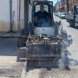 Ο ταύρος ολισθήσεων οδηγών εργαζομένων αφαιρεί τη φορεμένη άσφαλτο Στοκ Εικόνες