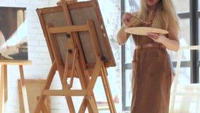 Ο ταλαντούχος καλλιτέχνης ενέπνευσε την εικόνα χρωμάτων στον καμβά που τοποθετήθηκε easel απόθεμα βίντεο