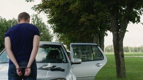 Ο τεθειμένος υπό κράτηση διαρρήκτης στις χειροπέδες στέκεται κοντά σε ένα κλεμμένο αυτοκίνητο απόθεμα βίντεο