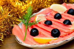 Ο τεμαχισμένος κόκκινος σολομός ψαριών πρασινίζει τις μαύρες ελιές λεμονιών στο πιάτο, ξύλινο καφετί υπόβαθρο, τοπ άποψη, εξυπηρέ Στοκ Φωτογραφία