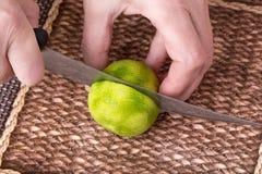 Ο τεμαχισμός ο ασβέστης με το μαχαίρι στοκ φωτογραφία