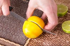 Ο τεμαχισμός το λεμόνι με το μαχαίρι στοκ φωτογραφία