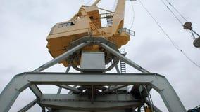 Ο τεράστιος βιομηχανικός γερανός στέκεται σε ένα καταστρέφοντας ναυπηγείο ενός εργοστασίου επεξεργασίας παλιοσίδερου στο νεφελώδη φιλμ μικρού μήκους