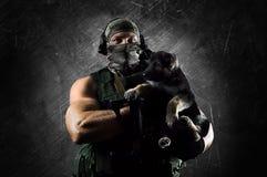 Ο τεράστιος στρατιωτικός κρατά ένα μικρό κουτάβι στα όπλα του στοκ φωτογραφία με δικαίωμα ελεύθερης χρήσης