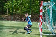 Ο τερματοφύλακας πιάνει τη σφαίρα Ο αθλητισμός σταδίων goalie παίζει το επίγειο παιχνίδι, άτομο φυλάκων ποδοσφαίρου χλόης, outdoo Στοκ φωτογραφία με δικαίωμα ελεύθερης χρήσης