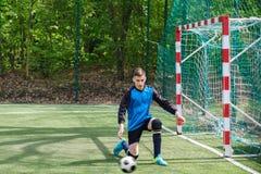 Ο τερματοφύλακας πιάνει τη σφαίρα Ο αθλητισμός σταδίων goalie παίζει το επίγειο παιχνίδι, άτομο φυλάκων ποδοσφαίρου χλόης, outdoo Στοκ Φωτογραφίες
