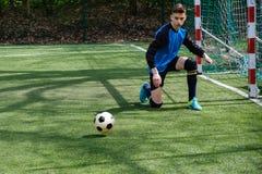 Ο τερματοφύλακας πιάνει τη σφαίρα Ο αθλητισμός σταδίων goalie παίζει το επίγειο παιχνίδι, άτομο φυλάκων ποδοσφαίρου χλόης, outdoo Στοκ εικόνα με δικαίωμα ελεύθερης χρήσης