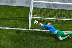Ο τερματοφύλακας ποδοσφαίρου ποδοσφαίρου που κάνει την κατάδυση σώζει Στοκ Φωτογραφίες