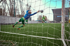 Ο τερματοφύλακας ποδοσφαίρου ποδοσφαίρου που κάνει την κατάδυση σώζει Στοκ Εικόνες
