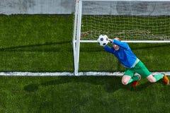 Ο τερματοφύλακας ποδοσφαίρου ποδοσφαίρου που κάνει την κατάδυση σώζει Στοκ Εικόνα