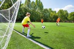 Ο τερματοφύλακας προσπαθεί να πιάσει το ποδόσφαιρο που ρίχνεται Στοκ Εικόνες