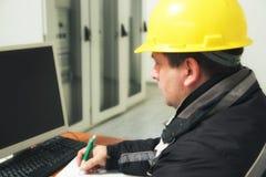 Ο τεχνικός παίρνει τις σημειώσεις στο κέντρο ελέγχου εγκαταστάσεων παραγωγής ενέργειας Στοκ εικόνες με δικαίωμα ελεύθερης χρήσης
