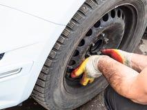 Ο τεχνικός συνδέει μια ρόδα χειμερινών αυτοκινήτων υπαίθρια στοκ φωτογραφία με δικαίωμα ελεύθερης χρήσης