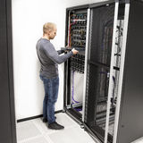 Ο τεχνικός ΤΠ εγκαθιστά το ράφι δικτύων στο datacenter στοκ εικόνες
