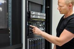Ο τεχνικός ΤΠ ελέγχει τον κεντρικό υπολογιστή στο ράφι σε Datacenter στοκ εικόνες