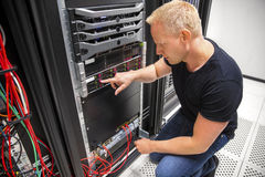 Ο τεχνικός ΤΠ ελέγχει τον κεντρικό υπολογιστή στο ράφι σε Datacenter στοκ φωτογραφίες