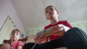 Ο τηλεοπτικός ελεγκτής παιχνιδιών παιχνιδιού παιδιών παιδιών παρηγορεί στο εσωτερικό παιχνίδι αγοριών και κοριτσιών on-line τα πα απόθεμα βίντεο