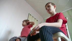 Ο τηλεοπτικός ελεγκτής παιχνιδιών παιχνιδιού παιδιών παιδιών παρηγορεί στο εσωτερικό gamepad παιχνίδι αγοριών και κοριτσιών on-li απόθεμα βίντεο