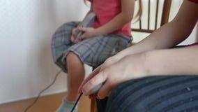 Ο τηλεοπτικός ελεγκτής παιχνιδιών παιχνιδιού παιδιών παιδιών παρηγορεί στο εσωτερικό το αγόρι και το κορίτσι gamepad παίζουν on-l απόθεμα βίντεο