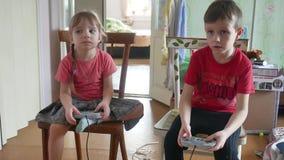 Ο τηλεοπτικός ελεγκτής παιχνιδιών παιχνιδιού παιδιών παιδιών gamepad στο εσωτερικό παρηγορεί παιχνίδι αγοριών και κοριτσιών on-li φιλμ μικρού μήκους