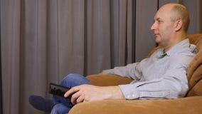 Ο τηλεχειρισμός λαβής λευκών και το χρησιμοποιεί για τον έλεγχο μέσων Το άτομο κάθεται στην πολυθρόνα και τη χρήση που ο τηλεχειρ φιλμ μικρού μήκους