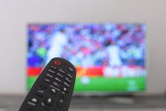 Ο τηλεχειρισμός με η TV στο υπόβαθρο θορίου στοκ εικόνα