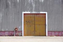 Ο τοίχος εργοστασίων μετάλλων φύλλων με την κόκκινη πόρτα εισόδων στο βιομηχανικό πάρκο Η κόκκινη πόρτα του κτηρίου εργοστασίων Στοκ εικόνα με δικαίωμα ελεύθερης χρήσης