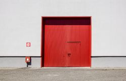 Ο τοίχος εργοστασίων μετάλλων φύλλων με την κόκκινη πόρτα εισόδων στο βιομηχανικό πάρκο Η κόκκινη πόρτα του κτηρίου εργοστασίων Στοκ Φωτογραφίες