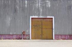 Ο τοίχος εργοστασίων μετάλλων φύλλων με την πόρτα εισόδων στο βιομηχανικό πάρκο Η κόκκινη πόρτα του κτηρίου εργοστασίων Στοκ Εικόνα