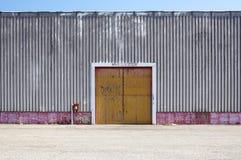 Ο τοίχος εργοστασίων μετάλλων φύλλων με την πόρτα εισόδων στο βιομηχανικό πάρκο Η κόκκινη πόρτα του κτηρίου εργοστασίων Στοκ φωτογραφία με δικαίωμα ελεύθερης χρήσης