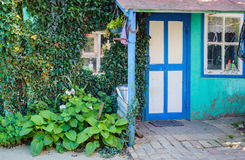 Ο τοίχος μπροστινών πορτών, παραθύρων και κισσών ενός παραδοσιακού του χωριού hou Στοκ Εικόνες