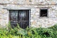 Ο τοίχος παραθύρων και κισσών μπροστινών πορτών ενός παραδοσιακού του χωριού hous Στοκ Εικόνα