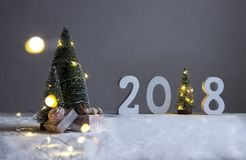 Ο τομέας κάτω από fir-trees, το σκυλί κοιμάται στα δώρα και στην απόσταση είναι σχήματα το 2018 όπου στο ρόλο ενός χριστουγεννιάτ Στοκ Εικόνες