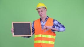 Ο τονισμένος πίνακας εκμετάλλευσης εργατών οικοδομών νεαρών άνδρων και το δόσιμο φυλλομετρούν κάτω απόθεμα βίντεο