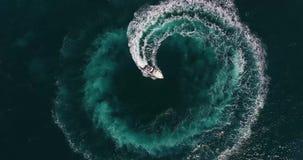 Ο τοπ αριθμός άποψης του κύκλου και της σπειροειδούς μορφής έκανε με τα foamy ίχνη ταχυπλόων στην κυανή ωκεάνια επιφάνεια νερού φιλμ μικρού μήκους