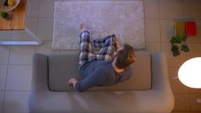 Ο τοπ βλαστός κινηματογραφήσεων σε πρώτο πλάνο των νεολαιών έντυσε άνετα την αρσενική TV προσοχής στον καναπέ στο εσωτερικό στο ά απόθεμα βίντεο