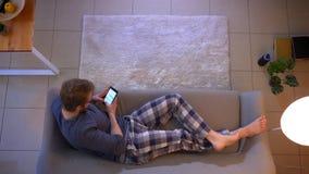 Ο τοπ βλαστός κινηματογραφήσεων σε πρώτο πλάνο των νεολαιών έντυσε άνετα το αρσενικό μήνυμα στο τηλέφωνο που βρίσκεται στον καναπ απόθεμα βίντεο