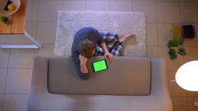Ο τοπ βλαστός κινηματογραφήσεων σε πρώτο πλάνο των νεολαιών έντυσε άνετα το αρσενικό χρησιμοποιώντας την ταμπλέτα με την πράσινη  απόθεμα βίντεο