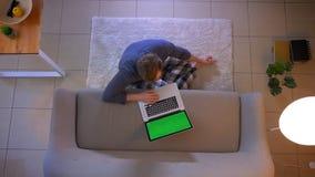 Ο τοπ βλαστός κινηματογραφήσεων σε πρώτο πλάνο των νεολαιών έντυσε άνετα την αρσενική δακτυλογράφηση στο lap-top με την πράσινη σ απόθεμα βίντεο