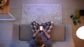 Ο τοπ βλαστός κινηματογραφήσεων σε πρώτο πλάνο των νεολαιών έντυσε άνετα αρσενικός on-line στο τηλέφωνο καθμένος στον καναπέ στο  φιλμ μικρού μήκους