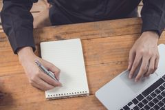 Ο τοπ επιχειρηματίας άποψης γράφει το σημειωματάριο και χρησιμοποίηση του lap-top στην ξύλινη ετικέττα Στοκ φωτογραφία με δικαίωμα ελεύθερης χρήσης