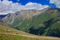 Ο τουρίστας αναρριχείται στον ανήφορο ιχνών, το βουνό βόρειου Καύκασου Στοκ Εικόνα