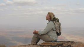 Ο τουρίστας γυναικών κάθεται πάνω από το βουνό και απολαμβάνει τις απόψεις και την επιτυχία φιλμ μικρού μήκους