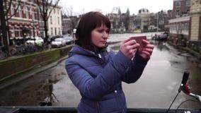 Ο τουρίστας γυναικών παίρνει pictureson στο smartphone την πόλη φυλακτών κίνηση αργή απόθεμα βίντεο